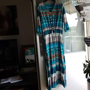 Lång klänning i fint skick med knappar hela vägen. Stl XL men liten i storleken.