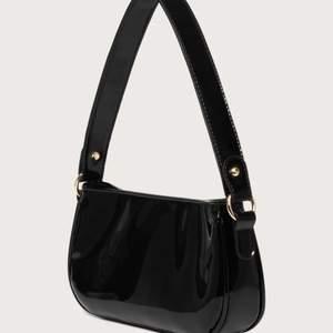 Supersnygg svart lackväska med guldiga detaljer😍 perfekt storlek för det viktigaste sakerna. Använd 2 gånger. Frakt tillkommer💓