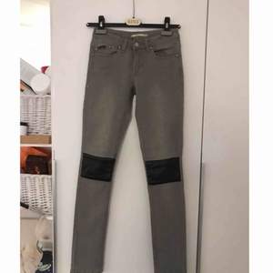 Gråa jeans med PU/läderdetaljer. Aldrig använda. Låg midja.