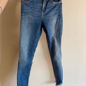 Blåa tighta jeans. På ena bakfickan har sömmen släppt lite, därav lite billigare.