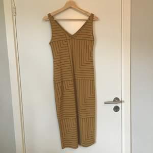 Vadlång mönstrad klänning i senapsgult och svart från Lindex. Gott skick. Frakt betalas av köparen.
