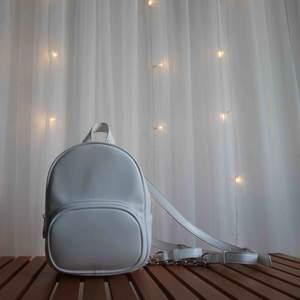 En vit mini backpack från FOREVER 21. Använd ett par fåtal gånger. Bredden är 17,5 cm och höjden 22,5 cm.