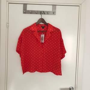 Helt ny med lappar kvar. Röd kortare blus med vita prickar! Underbart söt och perfekt till sommaren. Fram tillkommer på 32kr 🎈