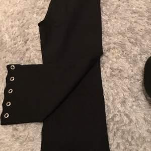 Ett par kostymbyxor som har metallhål nere vid ankeln, säger till billigt pris. Dom är så fina men använder inte längre för har växt ur dom. Frakt 30kr