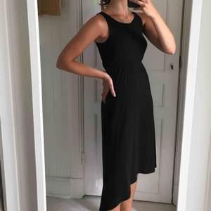 Trendig svart lång/medellång klänning. Väldigt skön och knappt använd. Kortare fram och längre bak🌞