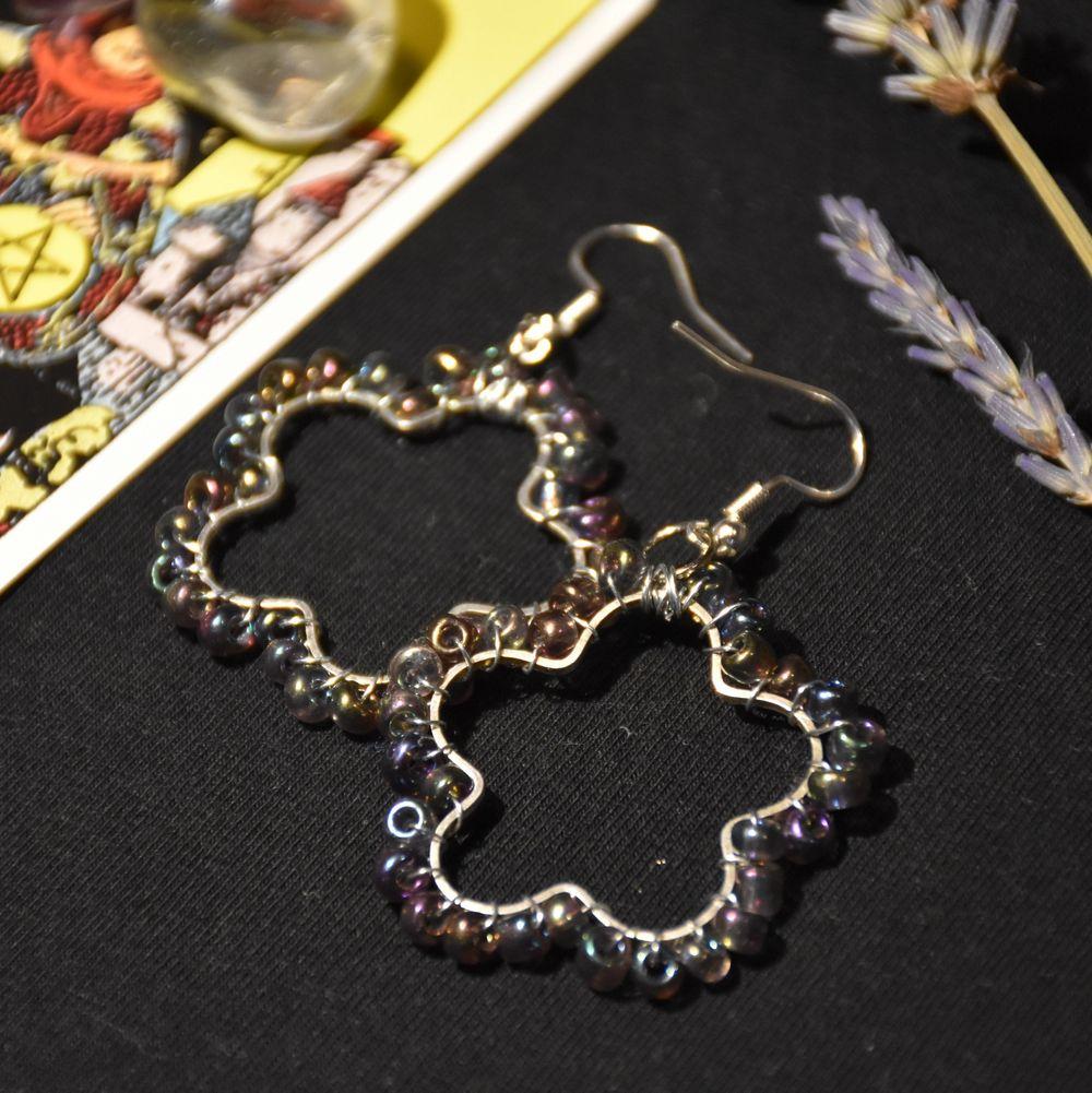 Örhängen med vackra lila regnbågsfärgade pärlor i form av blommor. Krokarna är nickelfria. . Accessoarer.