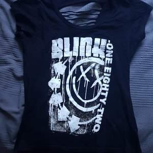 Blink-182 t-shit med hål i ryggen, syns på bild två. Har ett vitt papper så hålen ska synas bättre, tröjan är bara svart med vitt tryck! Den är använd en gång då jag ej var bekväm i den så priset är diskuterbart!