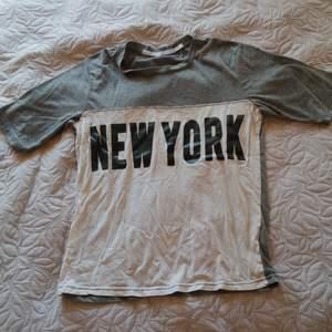 En grå och vit t-shirt med tryck från lager 157, använd ett fåtal gånger i mycket gott skick.