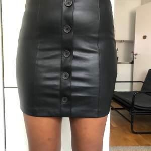 """En svart läderkjol med knappdetaljer på den främre delen, med en """"osynlig"""" dragkedja på baksidan. Stretchigt material!"""