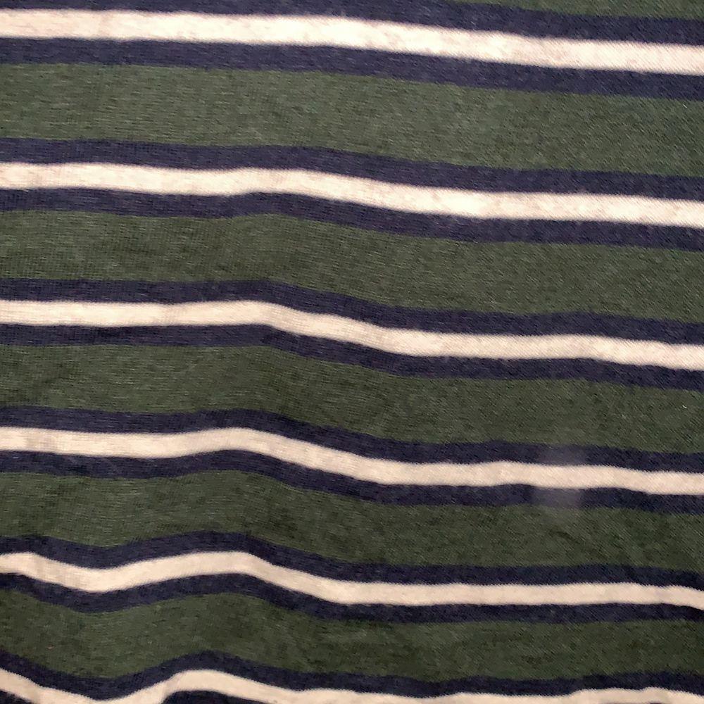 Croppad militära grön t-shirt med blå och vita ränder . T-shirts.