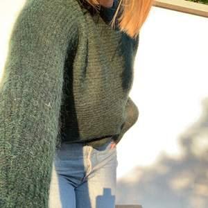 En stickad grön tröja med ett knuttars hål i ryggen. Den är från SPRITE och jag köpte den för 900kr i butik🥰