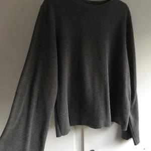 En grå tröja med lite bredere armar. Kan passa till storlek L & XL