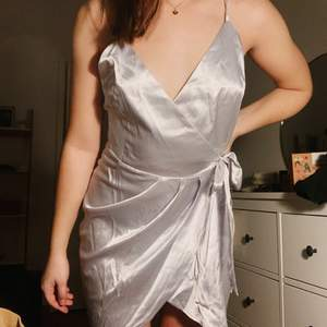 Skön, silvrig, satin omlottklänning. Storlek S med justerbara band och knyte runt midjan. Jag är 170cm och väger 64kg.