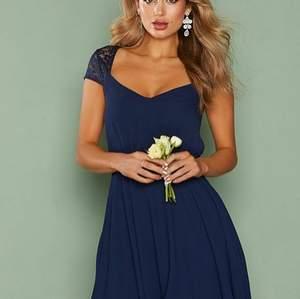 Mörkblå Nelly Eve klänning med spets på övre ryggen och axlarna. Nyskick, lapparna är kvar. Nypris: 499:-