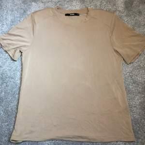 Beige T-shirt med axelvaddar. Från Bik Bok.. det är väldigt sladdrigt tyg vilket gör så att den ser dyr ut! Hehe.. storlek xsmall men den är lite större och sitter inte tajt på mig.