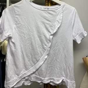 Vit topp / T-shirt med volang från Mango. Frakt tillkommer.