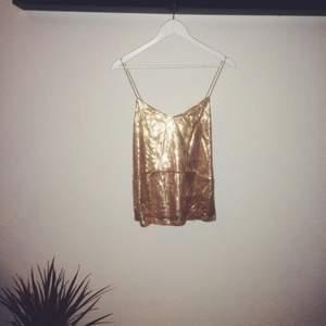 Paljettlinne i guld från Gina Tricot. Korsade band i ryggen och finns ett