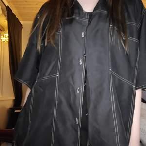 En svart skjorta som var populär på 80 talet. Väldigt tunt och luftigt material. Den är I storleken 38/40, själv bär jag S. Fint skick😊