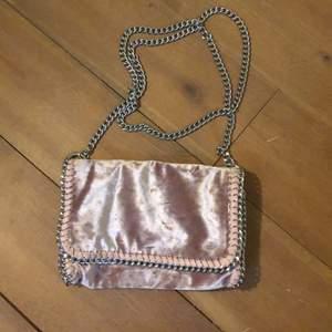 Sen rosa handväska i krossad sammet med en silverkedja från Gina Tricot. I väskan finns ett litet fack. Kan mötas upp i Stockholm men kan också frakta!
