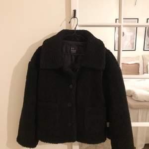 En svart, kort teddyjacka i storlek 34 🌼 använd ett fåtal gånger.