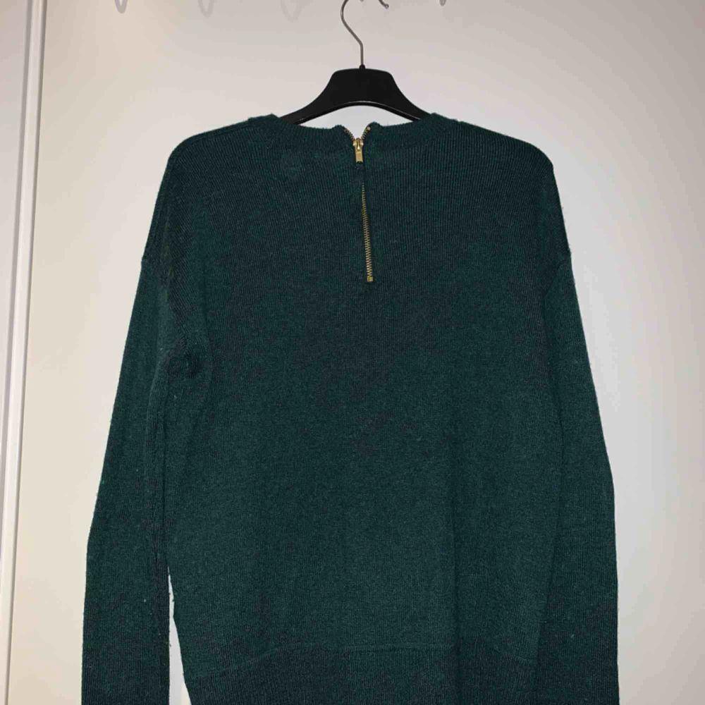 Stickad tröja med en guld dragkedja på baksidan. Ganska varm. Passar folk som brukar ha S. Använd typ 3 gånger. Stickat.