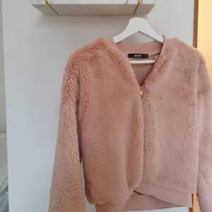 En rosa fluffig och mjuk kofta från BikBok. I storlek XS. Dragkedja i roseguld.