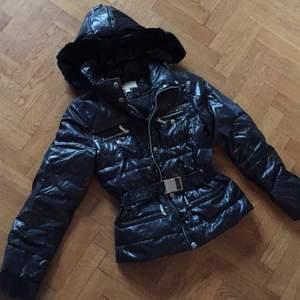 Michael Kors dunjacka med silverdetaljer, bälte i midjan som är avtagbart. Svart päls på luvan som är otroligt len! Varm och skön. Nypris ca 2300kr.