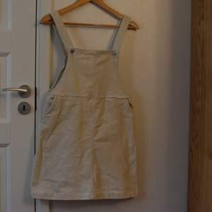 En klänning med hängslen som bara är använd ett fåtal gånger så de inte riktigt är min stil. Den är i off-white manchester. Storlek står inte men skulle kunna passa från s-m.