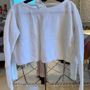 Stickad tröja (croppad) i fint skick! I ryggen sitter band som man kan välja att knyta i en fin rosett, alternativt om man vill klippa av dom så går det också😊