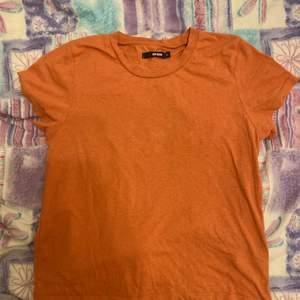 En mjuk t-shirt i en gosig orange nyans. Tröjan är i ett normalt skick och har använts minimalt. Perfekt att ha till en simpel outfit!
