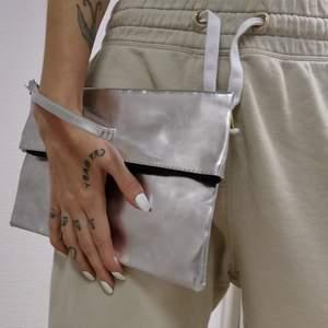 Liten silvrig väska med dragkedja. Rem att ha runt handen går även att ta av. Från hm. Frakt 42kr. Betalning swish.