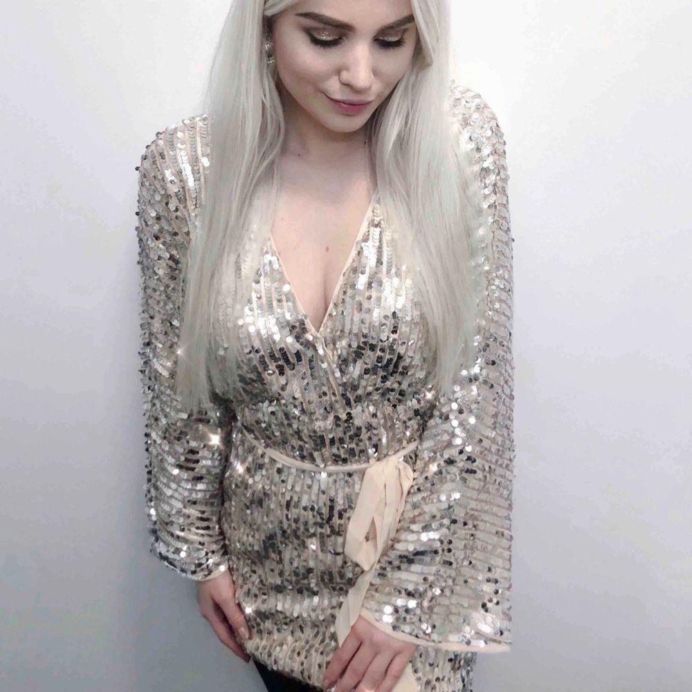 Glittrig klänning med bälte och vida ärmar. Storlek 38 (liten, passar 36), från Boohoo. Använd en gång.. Klänningar.