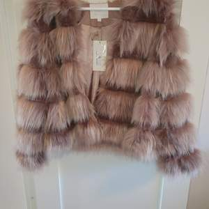 Rosa faux fur jacka i strl XS. Helt oanvänd, prislappen kvar.