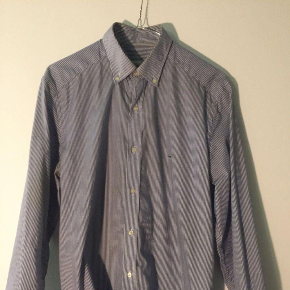 Blå/vit-randig skjorta från Lacoste, ganska slim passform.. Skjortor.
