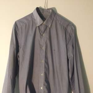 Blå/vit-randig skjorta från Lacoste, ganska slim passform.