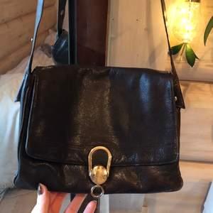 Mellanstor väska i brunt skinn med fint silverspänne
