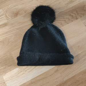 En svart mössa med tofs, vet tyvärr inte vart den är i från. Fraktkostnaden tillkommer.