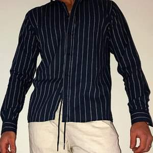 Bekväm stretchig skjorta ifrån Les Deux med 70% bomull och 30% polyester med bra pass form. Skjortan är något lång i varianten och kan med uppknäppta knappar vid armarna bli till en mer luftigare skjorta och i samma fall bli en mer slimmad skjorta med knapparna knäppta. Med material som är 70% bomull blir skjortan mycket bekväm och mjuk att ha på sig.