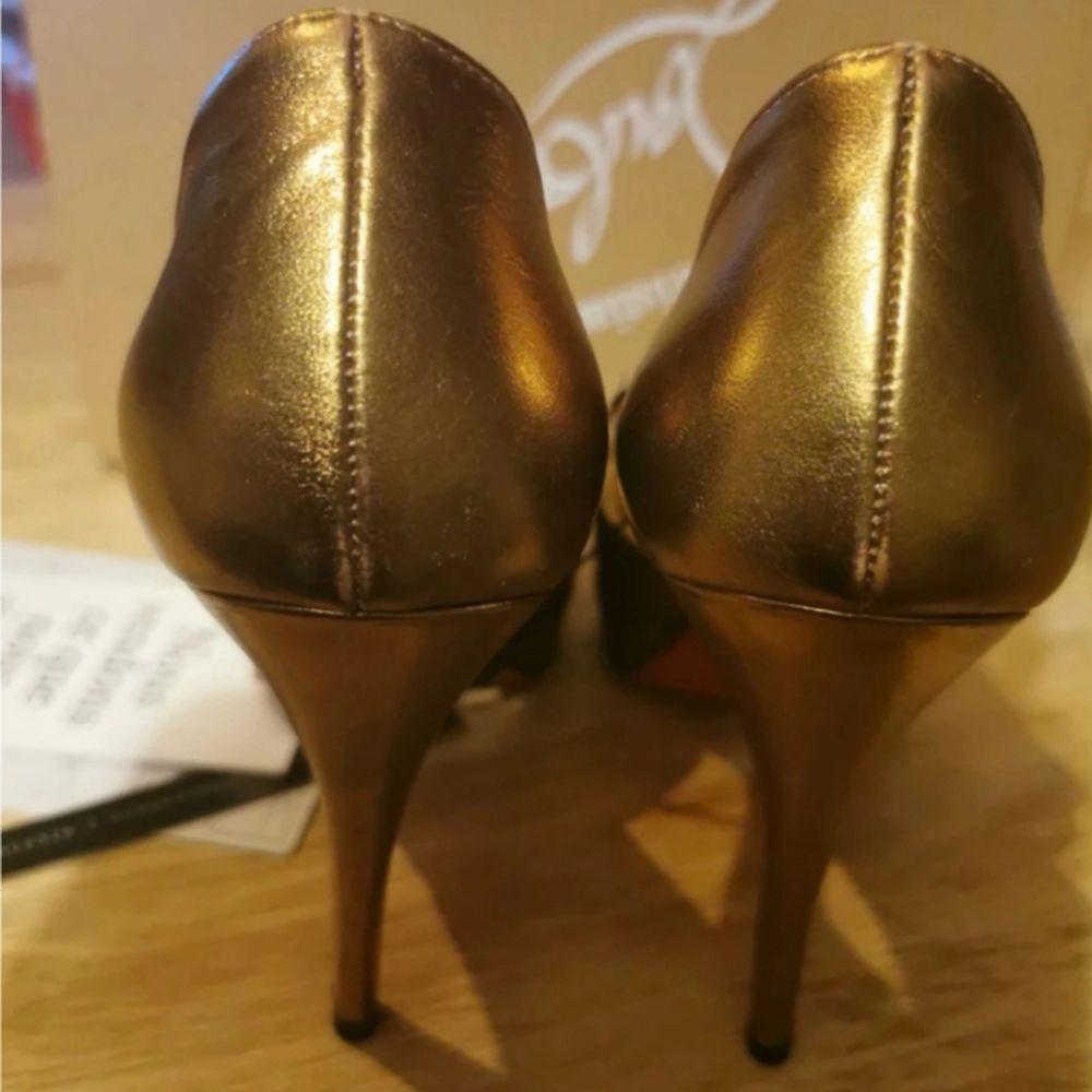 Inköpta på vestiaire collective, använda 1 gång på inomhus event. Passar en Stl 37 eftersom skorna är små i stl. Fint bronsfärgade. Kommer med sin box, alla tags från vestiaire samt dustbag. . Skor.