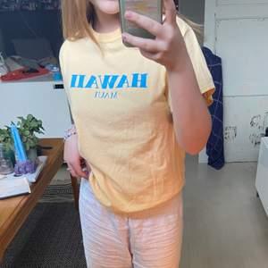 Snygg pastell gul T-shirt med pastell blått tryck på framsidan.   Denna har surf känsla och passar så bra till kjolar, shorts och jeans. Du kan verkligen ha den när som. Materialet är strävt så passformen inte säckar ihop. Så skön!