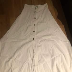 En jätte fin vit maxi kjol från HM, köpt förra sommaren, aldrig använd. Bruna knappar i fram. I storlek 36
