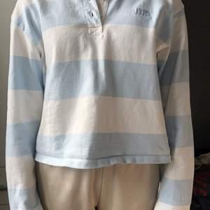 Blå randig tröja ifrån levi's som står i samma blå färg på höger sida!! Jätte fin 3knappar i mitten.