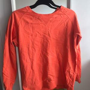 En korall färgad sweatshirt i storlek s/m