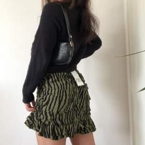 Världens finaste kjol som inte går att köpa längre. Den är helt ny med grön och svart mönster, har draperier som formar kroppen, volanger längst med kanten, en dold dragkedja på baksidan och är i M (passform S-M). En asymmetrisk söm vid vänstra låret och en symmetrisk bakom vid rumpan.  Startbud: 100kr exklusive frakt eller köp direkt 400kr exklusive frakt.