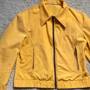 En gul vårjacka i biker/racer stil. Köpte denna i en vintagebutik i Aten. Möjligheten att kunna göra en kill bill utklädnad på halloween får heller inte glömmas! Den är i gott skick förutom två små fläckar som jag kan skicka bild på om det önskas <3