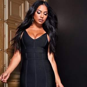 Elegant svart bandageklänning i stretchigt material och volag nertill