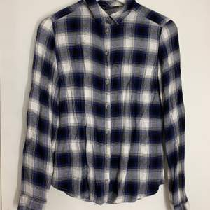 Rutig skjorta i en avslappnan modell. Köparen står för frakten.