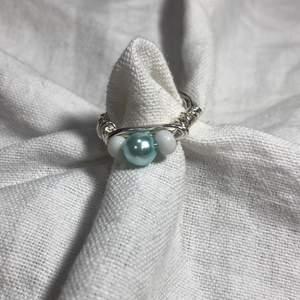 En hemmagjord ring med två små vita pärlor och en stor ljusblå pärla. Passar bra till mycket. 70kr med frakt!🚚