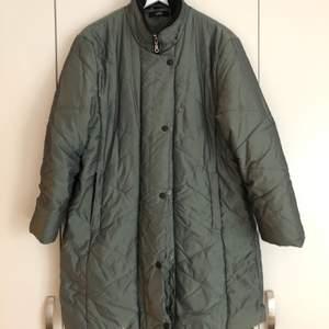 Fin quiltad lite längre jacka/kort kappa i en gröngrå färg. Storlek 40, men passar även fint på dig som är mindre. Retro/90tal i fint skick! Storleken kan justeras i insidan av midjan - se bild.