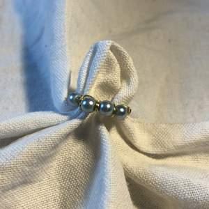 En hemmagjord ring med 4 blå/silvriga pärlor på. Metalltråden är i färgen guld. Passar bra till mycket. 70 kr med frakt 🚚